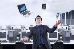 Businessperson juggling with business items. Portrait of happy businessman juggling with business items in the office Stock Image