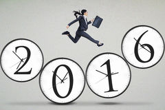 Businessperson jumping above the clock Stock Image