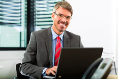 Businessperson with laptop in his business office royalty free stock image