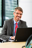 Businessperson with laptop in his business office Royalty Free Stock Photo