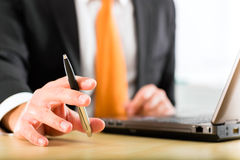 Businessperson with laptop in his business office Royalty Free Stock Photos