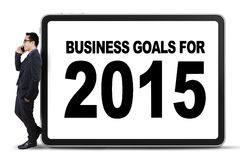 Businessperson leans on a business goals board Stock Images