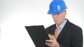 Businessperson Look i skrivplattapappersanmärkningar och att äta svultit en smörgås arkivfoton