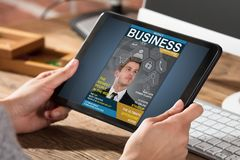 Businessperson Looking At Business Magazine. On Digital Tablet At Office Desk Royalty Free Stock Photography