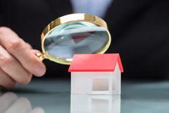 Businessperson Looking At House Modelthrough magnifying glass stock afbeelding