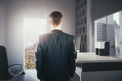 Businessperson looking at landscape. Businessperson standing in modern office interior with open door looking at landscape. Concept of choice between career Royalty Free Stock Images
