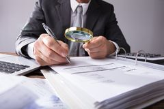 Businessperson Looking At Receipts Through Magnifying Glass stock photography