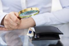 Businessperson with magnifier and wallet Stock Photography