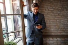 Businessperson med mobiltelefonen som kallar hans kamrat arkivbild
