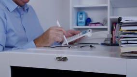 Businessperson met een in Hand Potlood maakt Berekeningen Gebruikend Rekenmachine stock video