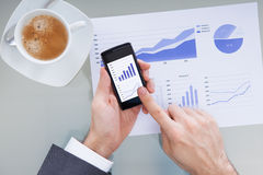 Businessperson With Mobile Phone Showing Graph Royalty Free Stock Photos