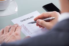 Businessperson with pen over checklist Royalty Free Stock Photo