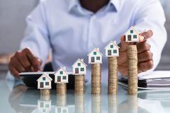 Businessperson Placing House Model On Coin Stacked royalty free stock photography