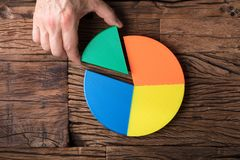 Businessperson Placing A Last Piece Into Pie Chart. High Angle View Of Businessperson`s Hand Placing A Last Piece Into Pie Chart stock photo