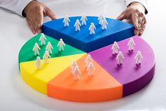 Businessperson placing last piece into pie chart. Businessperson placing last piece with human figures into colorful pie chart stock photos