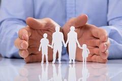 Businessperson Protecting Family Paper som ut klipps royaltyfria bilder