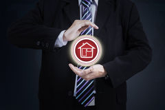 Businessperson protecting house icon Stock Images