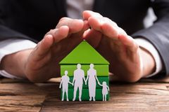 Businessperson Protecting House Model And Family Paper Cut Out. Businessperson`s Hand Protecting House Model And Family Paper Cut Out On Wooden Desk royalty free stock images
