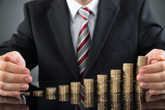 Businessperson Protecting Stack Of Coins Royalty Free Stock Image