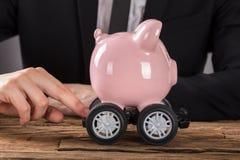 Businessperson Pushing Piggy Bank op Wielen stock foto's
