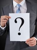 Businessperson with a question mark sign Stock Images