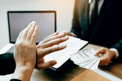 Businessperson refusing bribe given money by partner with anti bribery corruption concept.  royalty free stock photography