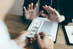 Businessperson refusing bribe given money by partner with anti bribery corruption concept.  stock images