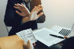 Businessperson refusing bribe given money by partner with anti bribery corruption concept.  stock photos