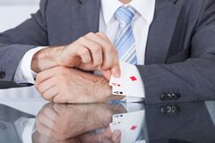 Businessperson removing ace from the sleeve. Close-up Of Businessperson Pulling Out A Hidden Ace From The Sleeve Stock Photography