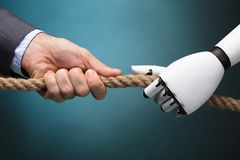 Businessperson And Robot Playing Tug Of War stock afbeelding