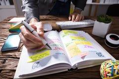Businessperson` s Hand het Schrijven Programma in Agenda met Pen royalty-vrije stock foto's