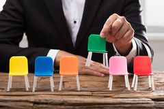 Businessperson`s hand picking up green chair stock photography