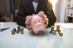 Businessperson`s Hand Shaking Piggy Bank stock photography