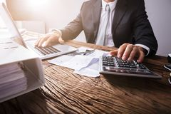 Businessperson`s Hand Using Calculator royalty free stock photography