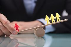 Businessperson Showing Imbalance Between Figures On Seesaw. Businessperson`s Hand Showing Imbalance Between Red Figure And Three Yellow Figures On Seesaw stock image