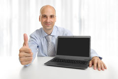 Businessperson showing a laptop with blank screen. For copy space stock photo