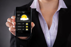 Businessperson Showing Weather Forecast op Mobiele Telefoon Stock Afbeelding