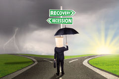 Businessperson with signboard to recovery or recession financial Royalty Free Stock Image