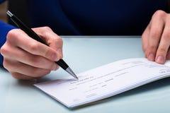 Businessperson Signing Cheque arkivbild