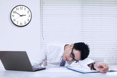 Businessperson sleeping in the office. Photo of young businessman sleeping on the desk with a clock on the wall, shot in the office Stock Photos