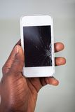 Businessperson smartphone with cracked screen. Close-up Of A Businessperson's Hand Holding Cellphone With Cracked Screen royalty free stock photography