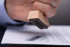 Businessperson Stamping Document. Close-up Of A Businessperson`s Hand Stamping Document royalty free stock images