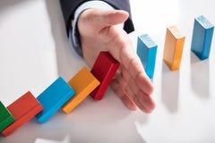 Businessperson Stopping Dominoes From die op Bureau vallen royalty-vrije stock afbeeldingen