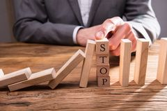 Businessperson Stopping Falling Dominos royalty-vrije stock foto