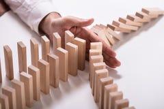 Businessperson Stopping Wooden Blocks van het Vallen royalty-vrije stock afbeelding