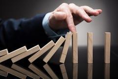 Businessperson Stopping Wooden Blocks van het Vallen op Bureau royalty-vrije stock afbeelding