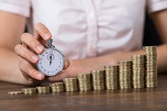 Businessperson With Stopwatch And Stack Of Coins Stock Photos