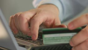 Businessperson typing bank card number on laptop, close-up of man's fingers. Stock footage stock video footage