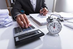 Businessperson Using Calculator For Calculating Bill. With Alarm Clock On Desk royalty free stock photos