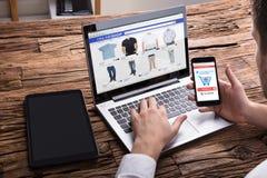 Businessperson Using Smartphone While som direktanslutet shoppar på bärbara datorn royaltyfri foto